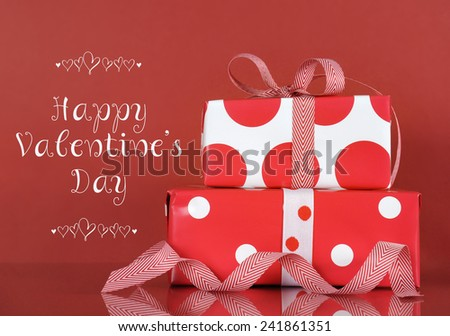 Happy Valentines Day stack of red and white gifts on red background with sample text greeting message. - stock photo