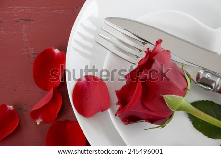 Happy Valentines Day table place setting on red vintage wood background with red rose, closeup overhead.