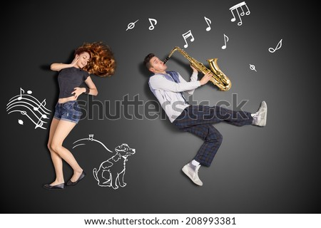 Happy valentines love story concept of a romantic couple against chalk drawings background. Male playing the sax for his girlfriend. - stock photo