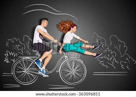 Happy valentines love story concept of a romantic couple against chalk drawings background. Male riding his girlfriend in a front bicycle basket. - stock photo