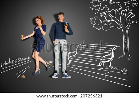 Happy valentines love story concept of a romantic couple in the park eating ice cream against chalk drawings background. - stock photo