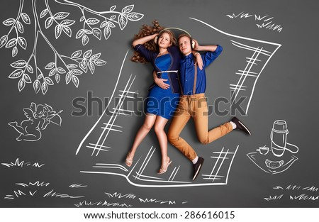 Happy valentines love story concept of a romantic couple on a picnic sharing headphones and listening to the music against chalk drawings background. - stock photo