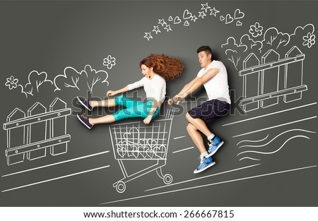 Happy valentines love story concept of a romantic couple on chalk drawings background. Male riding his girlfriend in a shopping cart along the street. - stock photo