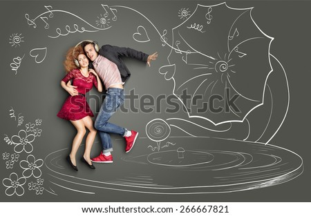 Happy valentines love story concept of a romantic couple sharing headphones, listening to the music and dancing on a gramophone, against chalk drawings background. - stock photo