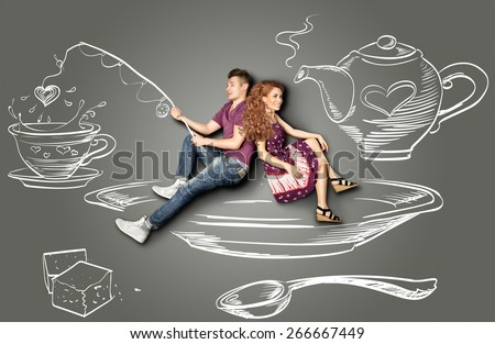 Happy valentines love story concept of a romantic couple sitting on a saucer and fishing in a teacup against chalk drawings background. - stock photo