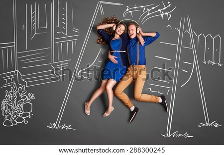 Happy valentines love story concept of a romantic couple sitting on the canopy swing sharing headphones and listening to the music against chalk drawings backyard background. - stock photo