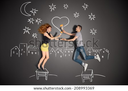 Happy valentines love story concept of a romantic couple standing on a stool and painting a heart in the night sky against chalk drawings background. - stock photo