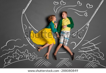 Happy valentines love story concept of a romantic couple swinging on the moon, holding hands and kissing against chalk drawings background of a night sky. - stock photo