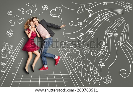 Happy valentines love story concept of a romantic couple walking in the park, sharing headphones and listening to the music against chalk drawings background. - stock photo