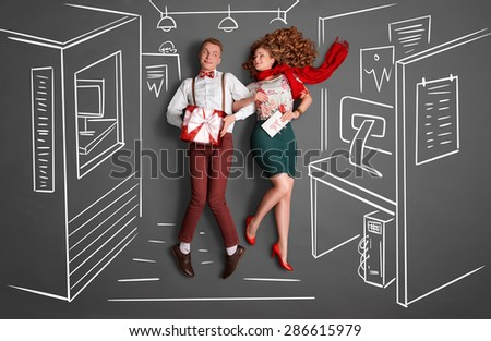 Happy valentines love story concept of an office romance. Young couple at work smiling at each other and sharing gifts against chalk drawings office background. - stock photo