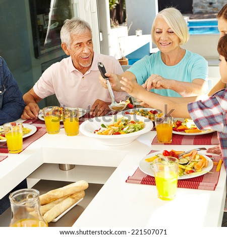 Happy vegetarian senior couple eating lunch with family - stock photo