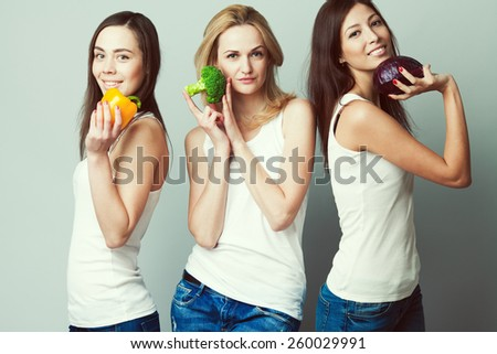 Happy veggies concept. Group portrait of healthy young women in white sleeveless shirts and blue jeans standing with vegetables & posing over gray background. Urban style. Studio shot - stock photo