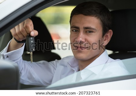Happy vehicle buyer inside his new car with car key - stock photo