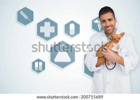 Happy vet checking dog with stethoscope against blue medical interface with icons - stock photo