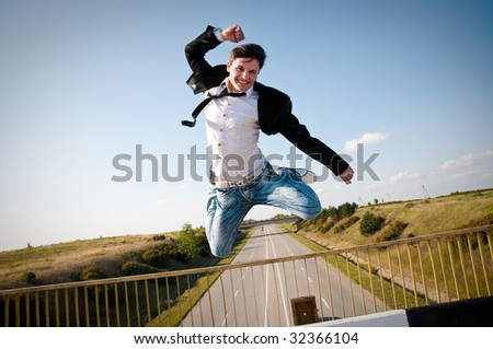happy victorious man jumping to the sky on the bridge - stock photo