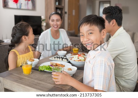 Happy Vietnamese boy with a glass of orange juice at the family dinner table - stock photo