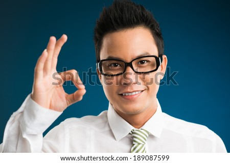 Happy Vietnamese businessman showing ok sign - stock photo
