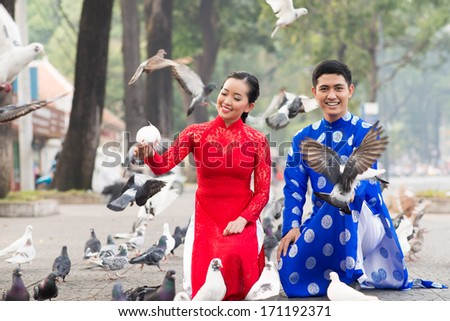 Happy Vietnamese couple among pigeons on the street