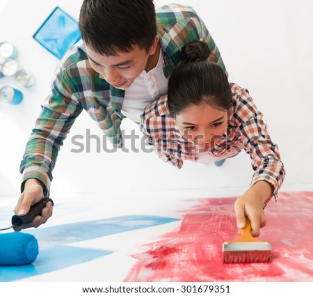 Happy Vietnamese couple painting the wall in new house: moving and renovation concept