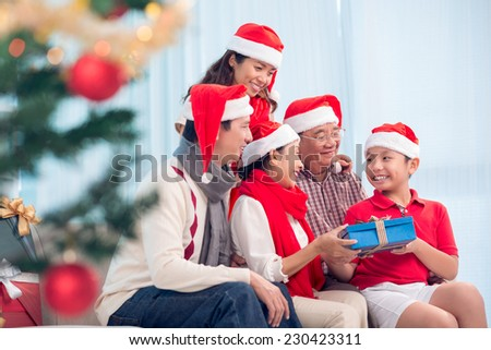 Happy Vietnamese family gathered together to exchange Christmas presents - stock photo