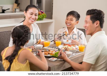 Happy Vietnamese family laughing while having dinner - stock photo