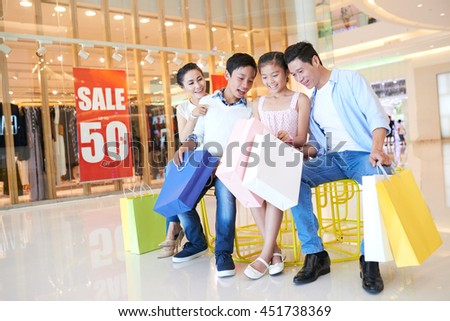 Happy Vietnamese family looking at purchases they made