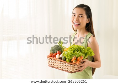 Happy Vietnamese girl carrying basket with homegrown vegetables