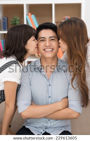 Happy Vietnamese man being kissed by two girls - stock photo