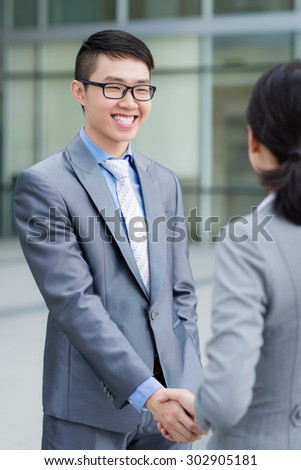 Happy Vietnamese manager greeting his female business partner