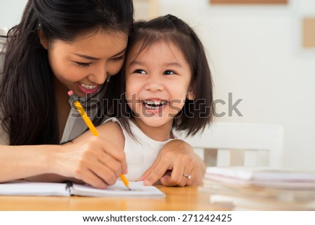 Happy Vietnamese mother and daughter drawing together - stock photo