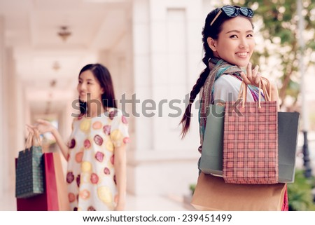 Happy Vietnamese shopaholic with paper bags and her friend in the background - stock photo