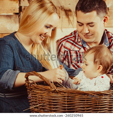 Happy village family, mom and dad playing with a small child sitting on the hay - stock photo