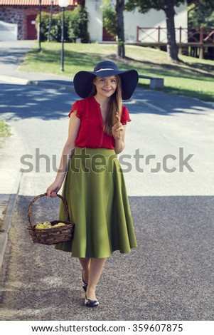 Happy village woman is carrying green apples - stock photo