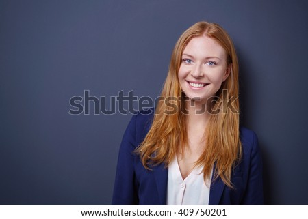 Happy vivacious young businesswoman posing against a dark studio background with copy space looking at the camera with a beaming smile - stock photo