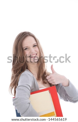 Happy vivacious young woman carrying her college textbooks under her arm giving a thumbs up gesture of approval and success isolated on white