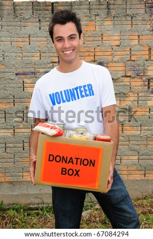 happy volunteer carrying a food donation box - stock photo
