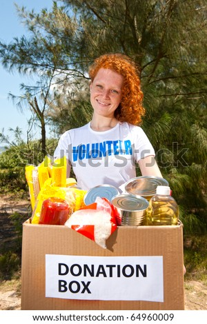 happy volunteer carrying food donation box - stock photo