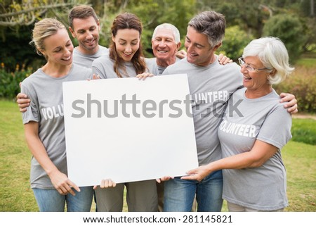Happy volunteer family holding a blank on a sunny day - stock photo
