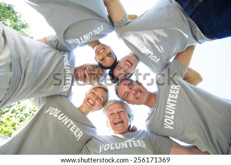 Happy volunteer family looking down at the camera on a sunny day - stock photo