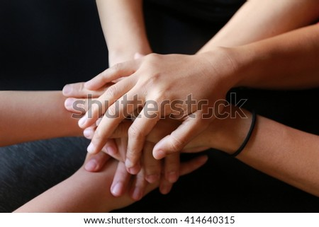 Happy volunteer family putting their hands together - close up of creative team sitting at table and holding hands on top of each,  teamwork hand group