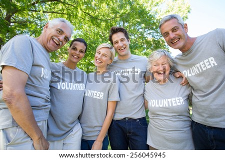 Happy volunteer family smiling at the camera on a sunny day - stock photo