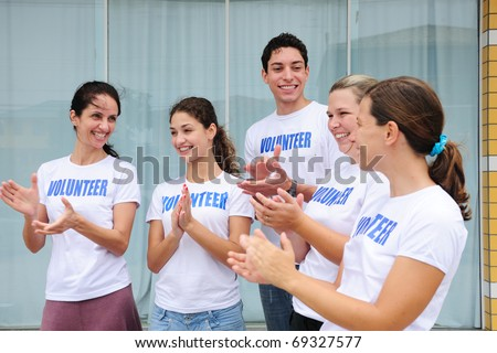 happy volunteer group applauding and laughing - stock photo