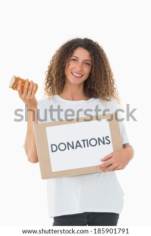 Happy volunteer holding a box of donations and jam jar on white background - stock photo