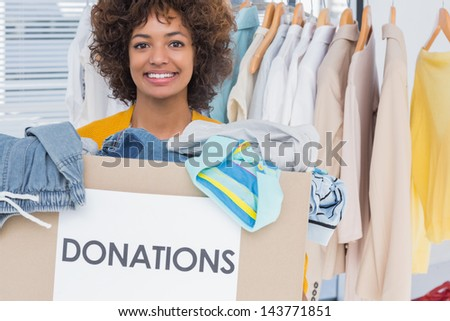 Happy volunteer smiling and holding donation box - stock photo