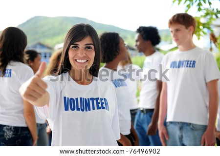 happy volunteer woman showing thumbs up sign, group in background - stock photo