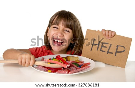 happy vulnerable 4 or 5 years old female child asking for help  eating dish full of candy holding sugar spoon in sweet abuse dangerous diet and unhealthy nutrition concept isolated on white - stock photo
