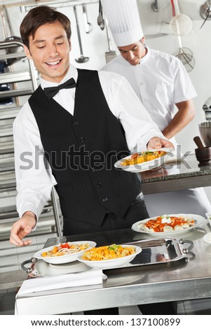 Happy waiter holding pasta dish with chef in background