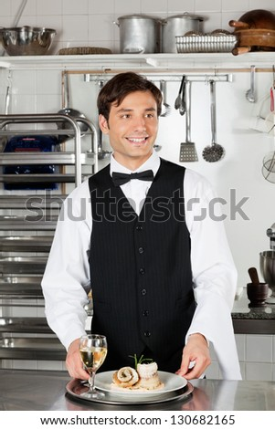 Happy waiter with salmon roll and white wine in tray standing at kitchen counter
