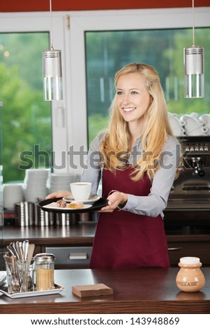 Happy waitress serving coffee with sweet food at counter
