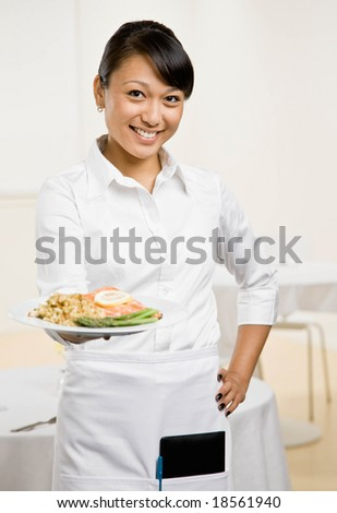 Happy waitress serving healthy dinner of salmon and asparagus